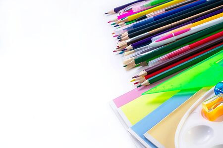A lot of multi-colored school and office supplies on a white background. Back to school. Copyspace for text.