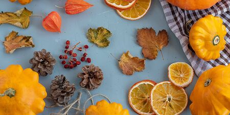 Bright autumn background. Top view of a white and brown checked kitchen towel, orange pumpkin, yellow squash, autumn leaves, physalis, cones, dried orange slices, flat lay, thanksgiving concept. Banner Banque d'images - 135237330