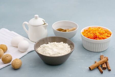 Ingredients for baking carrot cake. Flour, grated carrots, eggs, milk, walnuts, spices are located on the kitchen table in gray. Carrot cake day Banque d'images - 135237332