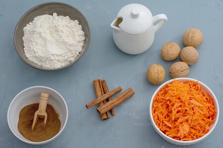 Ingredients for baking carrot cake. Flour, grated carrots, milk, walnuts, spices are located on the kitchen table in gray. Carrot cake day Banque d'images - 135237333