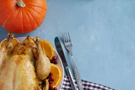 A fried chicken dish, pumpkin, cutlery and a white and brown checkered kitchen towel or cotton napkin lie on the table. View from above. Copy space for text. Can be used as a layout for design. Culinary background. Thanksgiving Day Banque d'images - 135237252