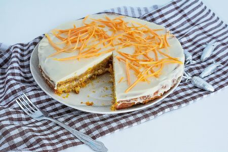 Homemade carrot cake with cream and a white and brown checkered towel on a white kitchen table. Vegan and Gluten Free Carrot Cake. Carrot cake Banque d'images - 135237255