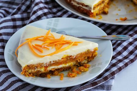 A slice of homemade carrot cake with cream and a white and brown checkered towel on a white kitchen table. Vegan and Gluten Free Carrot Cake. Carrot cake Banque d'images - 135237256