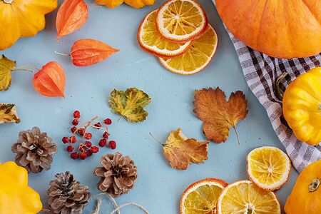 Bright autumn background. Top view of a white and brown checked kitchen towel, orange pumpkin, yellow squash, autumn leaves, physalis, cones, dried orange slices, flat lay, thanksgiving concept. Banque d'images - 135237274