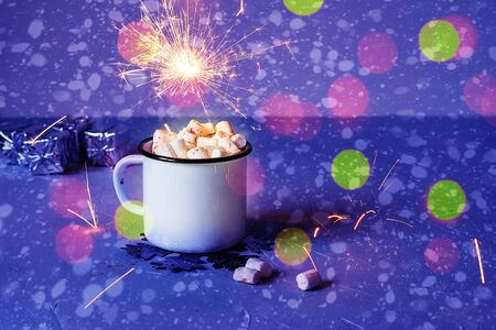 White metal mug of cocoa or hot chocolate with marshmallows on a table with New Year's decor and sparkling bokeh lights in the background. Christmas house concept. Banque d'images - 135237279