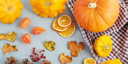 Bright autumn background. Top view of a white and brown checked kitchen towel, orange pumpkin, yellow squash, autumn leaves, physalis, cones, dried orange slices, flat lay, thanksgiving concept. Banner. Banque d'images - 135237224