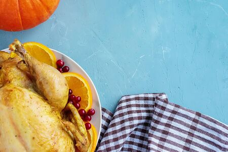 A fried chicken dish, pumpkin and a white and brown checkered kitchen towel or cotton napkin lie on the table. View from above. Copy space for text. Can be used as a layout for design. Culinary background. Thanksgiving Day. Banque d'images - 135237230