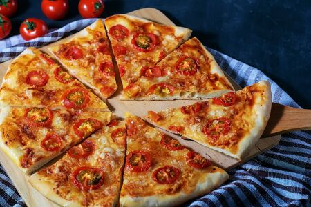 Freshly baked homemade pizza sliced in pieces lies on a black table. Banque d'images - 135455571