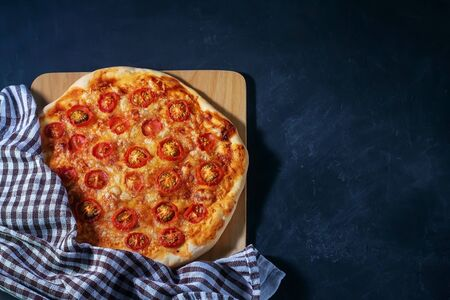 Freshly baked homemade pizza Margherita lies on a black background Banque d'images - 135585228