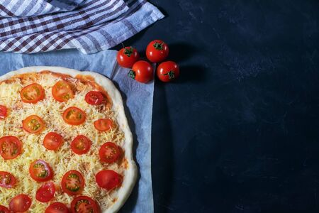 Raw Margarita pizza lies on a baking paper on a black background. Banque d'images - 135821652