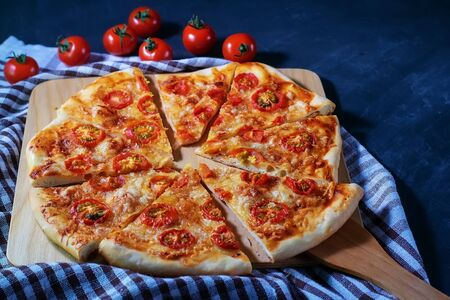 Freshly baked homemade pizza Margherita cut into pieces lies on a black background Banque d'images - 136173985