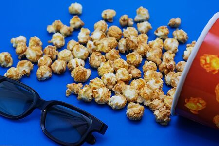 Caramel popcorn scattered on a blue background and 3D glasses for watching a movie. The concept of the film. Food for watching movies. View from above. 2020 blue color background. Banque d'images - 136341251