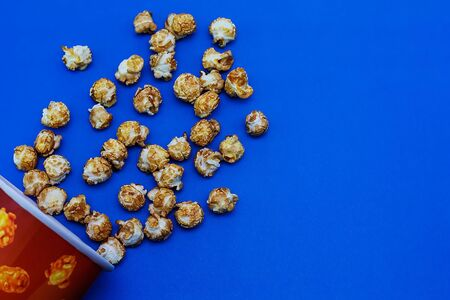 Caramel popcorn scattered on a blue background. The concept of the film. Food for watching movies. View from above. 2020 blue color background. Banque d'images - 136621314