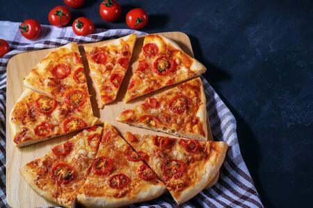 Freshly baked homemade pizza sliced in pieces lies on a black table. Banque d'images - 136705887