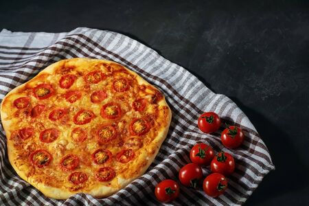 Freshly baked homemade pizza Margherita lies on a black background Banque d'images - 136797435