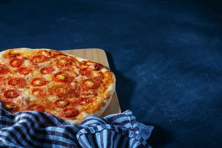 Freshly baked homemade pizza lies on a black wooden table. Banque d'images - 136914914