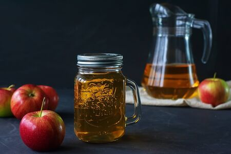 Glass jar of juice and jug with fresh fruits on a dark background. Summer refreshing drink. Banque d'images - 137480099