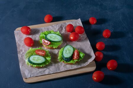 Bread with cucumber, lettuce and tomatoes. Sandwiches on a dark background. Selective focus. Healthy food, diet and nutrition concept. Banque d'images - 137572841