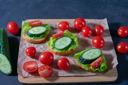 Bread with cucumber, lettuce and tomatoes. Sandwiches on a dark background. Selective focus. Healthy food, diet and nutrition concept. Banque d'images - 137572320