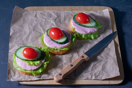 Sandwich with cucumber, lettuce, ham and tomatoes. Sandwiches on a dark background. Selective focus. Healthy food, diet and nutrition concept. Banque d'images - 137572897