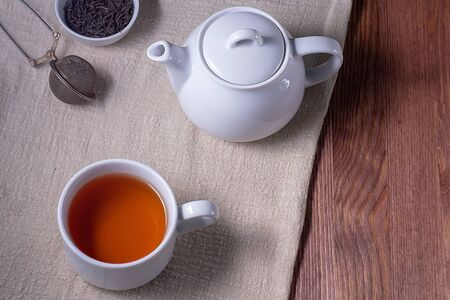 Tea. Cup of tea and teapot on a dark wooden table. Top view, copyspace. Banque d'images - 137848566