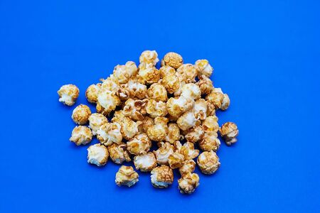 Caramel popcorn on a blue background. Movie concept. Food for watching movies. View from above. 2020 blue background color. Banque d'images - 138172094
