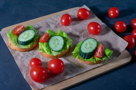 Bread with cucumber, lettuce and tomatoes. Sandwiches on a dark background. Selective focus. Healthy food, diet and nutrition concept.