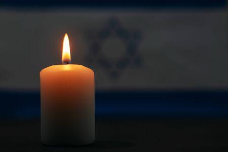 Brennende Kerze auf dem Hintergrund der Flagge Israels. Gedenktag.