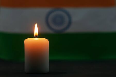 Brennende Kerze auf dem Hintergrund der Flagge Indiens. Gedenktag.
