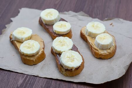 Sandwiches with peanut butter and chocolate paste with banana slices on a dark background. Home Fast Food Concept.