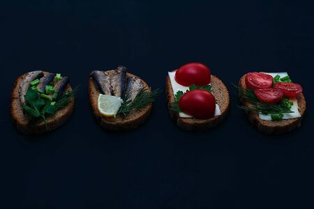 A variety of sandwiches with various fillings on a dark background. Sandwiches with sprats, with sardines on bread with herbs and sandwiches with tomatoes on a dark background. Food photography. Sandwich concept for breakfast or picnic. Stock Photo