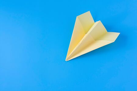 Yellow paper origami plane on a blue background. Close-up.
