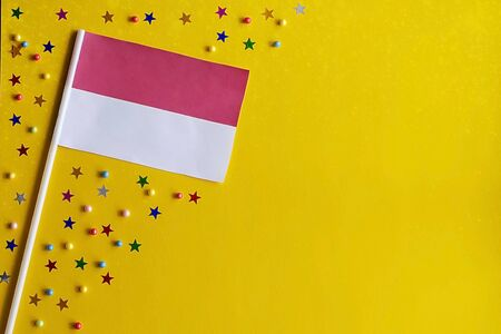 ndonesia Independence Day. Flag of Indonesia on a festive yellow background. The concept of celebration, patriotism and celebration. Copy space. Flat lay.