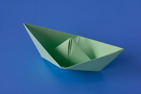 Paper boat on a blue background. Columbus Day