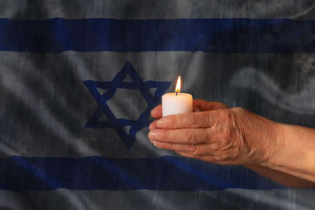 Hands hold a burning candle against the background of the flag of Israel. Day of Remembrance