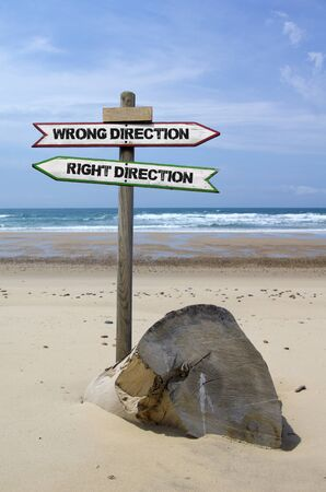 Double directional signs on a beach � wrong direction  right direction photo