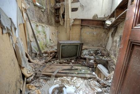 habitacion desordenada: Tv quebrada en una casa abandonada
