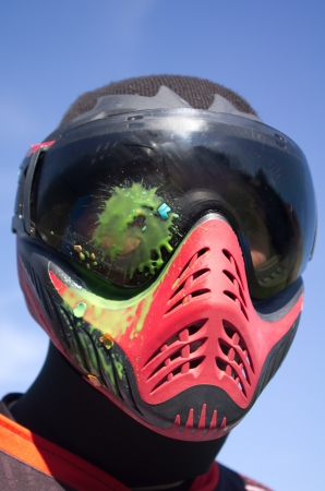 Paintball sport player with head shot by paint spot Stock Photo