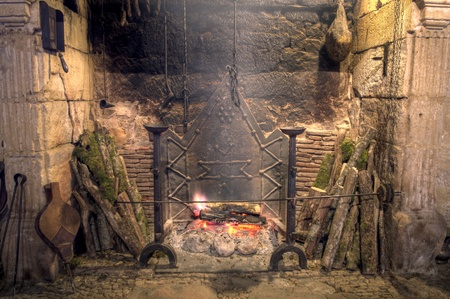 Stone fireplace with antique equipment in medieval castle