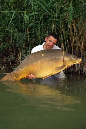 Happy  fisherman holding a giant mirror carp