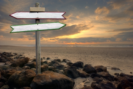 Double directional signs on a beach at sunset
