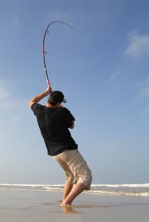 gevangen: surf vissen - vechten met een zeebaars Stockfoto
