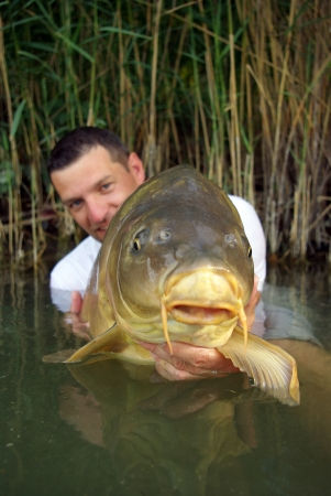 Lucky  fisherman holding a large mirror carp