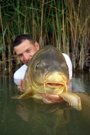 Pêcheur chanceux tenue d'une carpe miroir de grande Banque d'images - 15199664