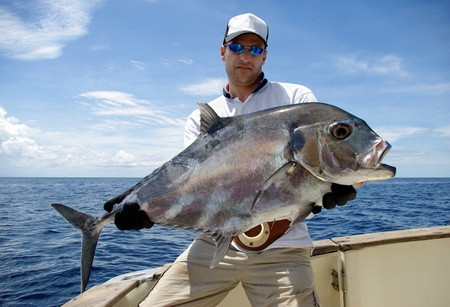 big game fishing: Happy  fisherman holding a giant trevally jack Stock Photo