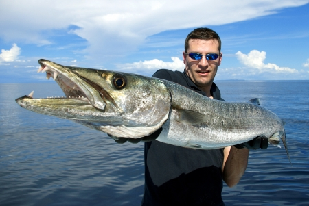 bateau de peche: P�cheur chanceux tenant un barracuda g�ant