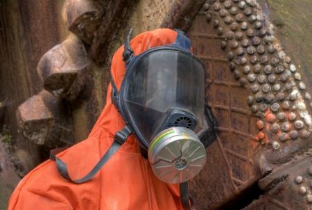 mascara de gas: Hombre con traje naranja de protección y máscara de gas Foto de archivo