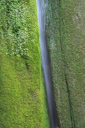 Beautiful waterfall between rocks covered by moss photo