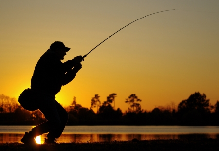 A fisherman fight against a fish at sunset photo