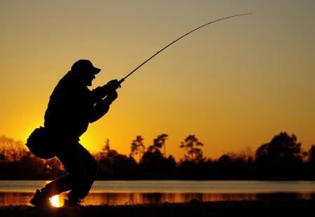 spigola: Una lotta contro un pesce pescatore al tramonto Archivio Fotografico